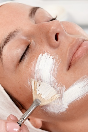 Closeup portrait of young woman having facial mask applied by beautician. photo