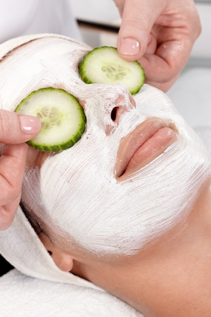 Natural facial treatment, young woman laying with facial mask and cucumber on eyes. photo