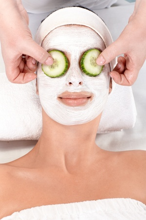 Natural beauty treatment with facial mask and cucumber. photo