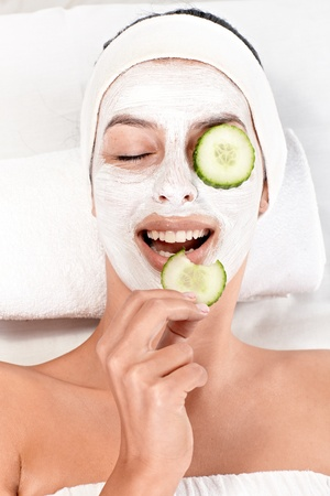 beauty salon face: Young woman having face mask and cucumber on eyes, biting cucumber, smiling. Stock Photo