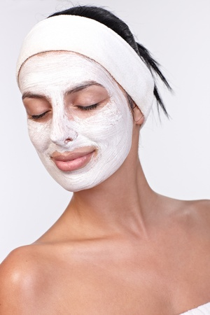 Young woman smiling with facial mask on, eyes closed, over white background. photo