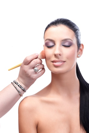 Beautiful female model with bare shoulders having makeup applied by makeup artist. Stock Photo - 13180192