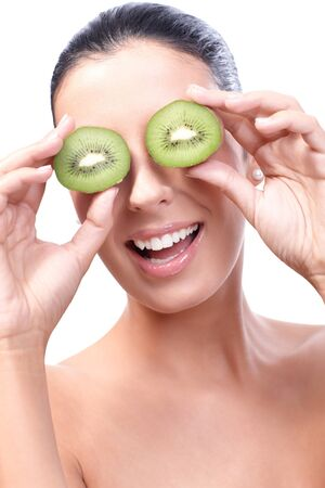 Smiling healthy woman placing half kiwi front of eyes. Stock Photo - 13180270