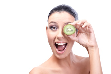 Attractive healthy woman placing kiwifruit front of left eye, laughing, looking at camera. Stock Photo - 13180158