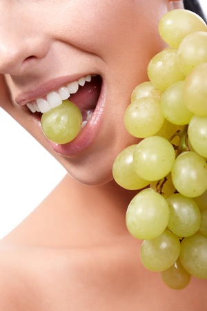 Closeup female lips eating grapes, holding a grape between teeth. photo