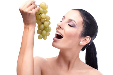 Young woman eating grapes with passion, eyes closed. Stock Photo - 13180177