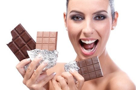 Happy young woman holding three chocolate bars in hand, smiling happily. photo