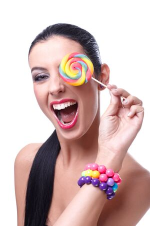 Attractive wild woman laughing, holding colorful lollipop over left eye. Stock Photo - 13212813