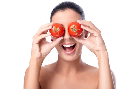 Healthy young woman holding tomatos over her eyes, laughing, bare shoulders. Stock Photo - 13212643