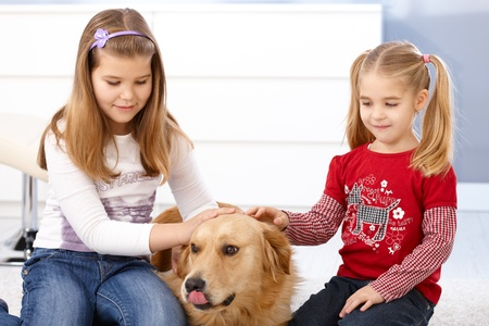 schoolgirls: Little girls stroking golden retriever, smiling.