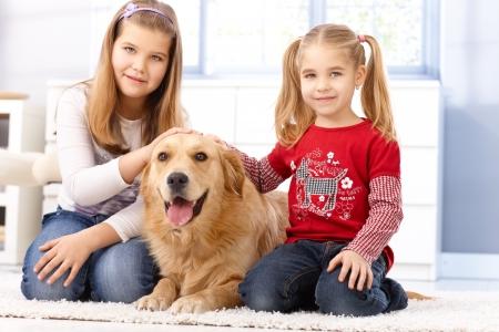 two stroke: Hermanitas de rodillas en el piso en su casa, acariciando mascota golden retriever, sonriendo. Foto de archivo