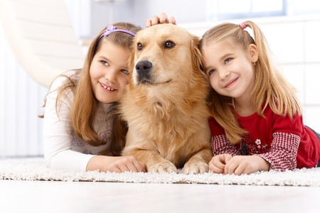 two stroke: Cute little girls lying prone on floor huddling up against golden retriever, smiling.