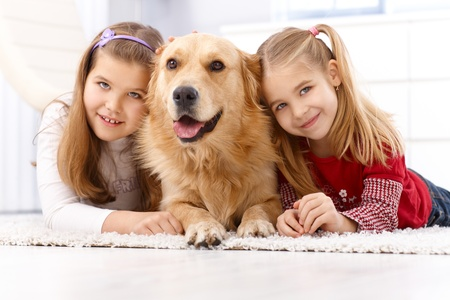 prone: Happy little girls lying prone on floor at home with golden retriever, smiling.