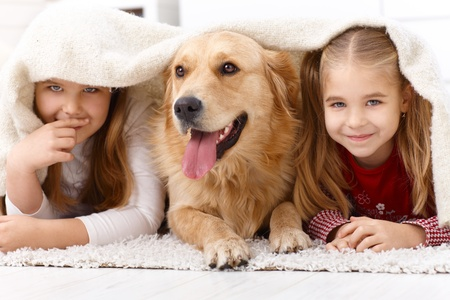 carpet color: Cute little girls having fun with golden retriever, lying prone on floor at home under blanket, smiling.
