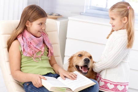 Little sisters smiling impishly, dog between them. photo