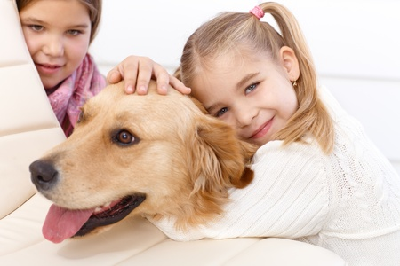 Little girl hugging golden retriever with love, older sister in background. photo