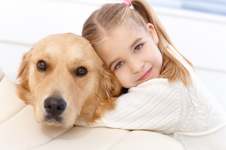 cuddles: Cute little girl hugging golden retriever with love, looking at camera.