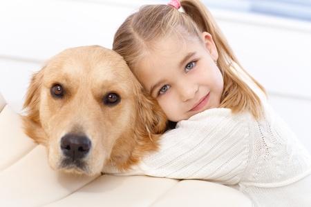 personas abrazadas: Linda ni�a abrazando perro perdiguero de oro con el amor, mirando a la c�mara. Foto de archivo