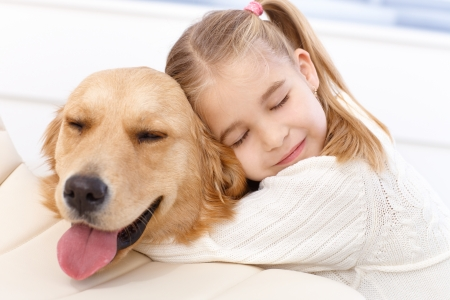 cuddles: Lovely little girl hugging pet dog with passion, eyes closed.