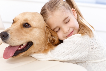 to cuddle: Cute little girl hugging golden retriever with love eyes closed, smiling.