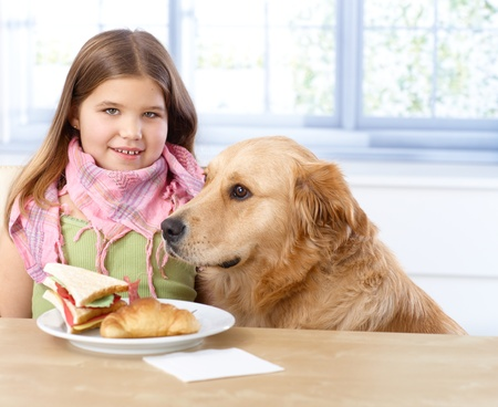 Portrait of little girl sitting at table having lunch, dog sitting next to her. photo