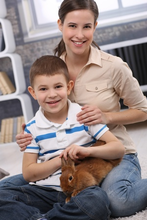 Portrait of young mum and cute son with pet rabbit in living room. Stock Photo - 13214583
