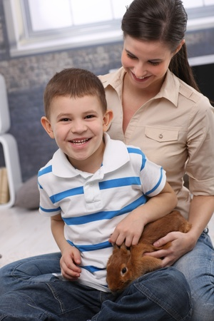 Happy portrait of laughing preschooler boy with mother playing with pet bunny at home. photo