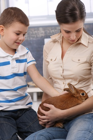 Cute kid and mum stroking pet bunny at home. photo