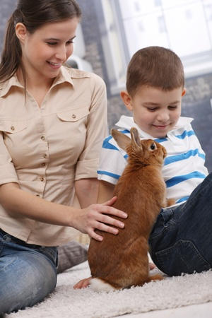 tenderly: Young attractive mother and smiling son playing with cute pet bunny at home. Stock Photo