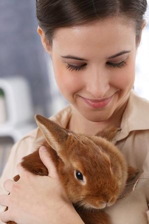 Portrait of happily smiling woman holding cute pet rabbit. photo