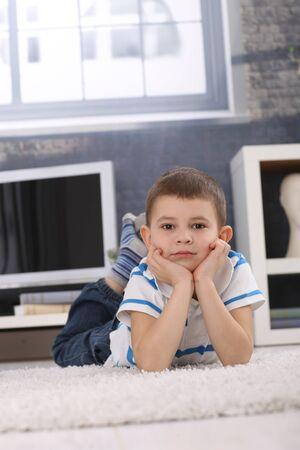 Retrato de niño lindo niño en edad preescolar acostado en el piso sala de estar, con la barbilla en las manos, mirando a la cámara.