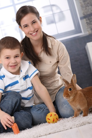 good looking boy: Happy mum and little son playing with domestic rabbit at home, carrot and ball.