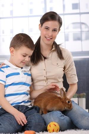 Portrait of happy little kid with mum caressing cute rabbit pet, smiling. photo