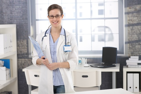 Happy young female doctor standing in office with clipboard handheld, smiling at camera. photo