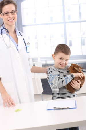 Smiling kid holding pet rabbit at veterinary office. photo