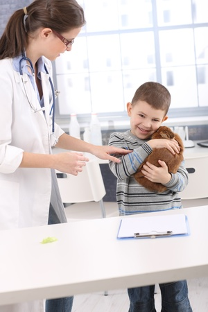 animal health: Smiling boy cuddling with pet rabbit at vet office, doctor trying to check animal.