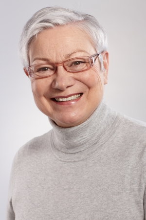 Closeup portrait of smiling elderly lady in grey sweater and glasses. photo