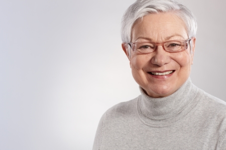 good looking woman: Portrait of elderly lady smiling in glasses and polo-neck sweater.