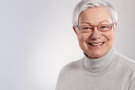 vecchiaia: Ritratto di donna anziana sorridente con gli occhiali e maglione a collo polo.
