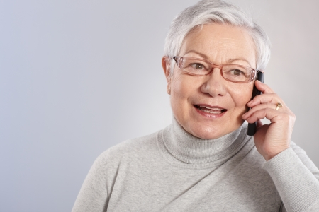 Old lady talking on mobile phone, smiling, looking away. Stock Photo - 13934125