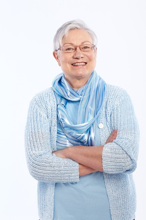 Smiling elderly lady standing arms crossed, looking at camera.