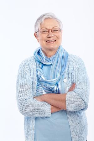 senior adult women: Smiling elderly lady standing arms crossed, looking at camera.