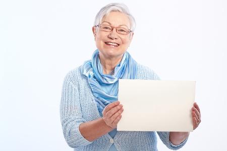 hoja en blanco: Se�ora mayor feliz que sostiene la hoja en blanco en la mano, sonriendo.