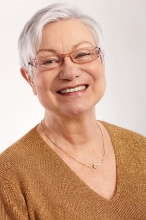 grannies: Closeup portrait of happy granny smiling in glasses and elegant sweater.
