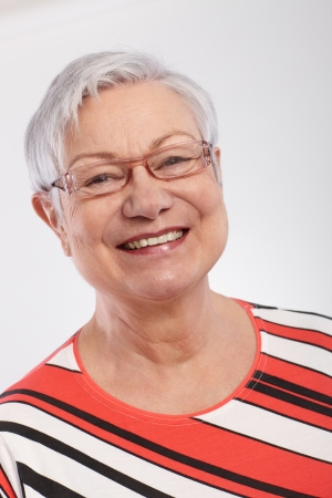 Closeup portrait of smiling old lady in stripy top   65533; photo