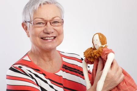 Grandmother holding rag doll, smiling, looking at camera   65533; Stock Photo - 13944802