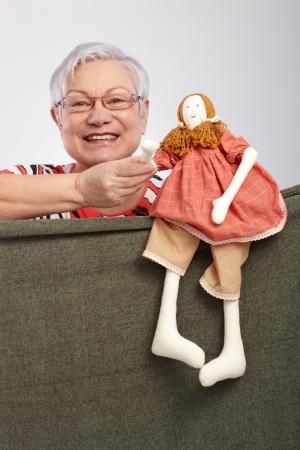 puppet woman: Se�ora de edad jugando al teatro de t�teres, sosteniendo la mu�eca t�tere en la mano, sonriendo 65533; Foto de archivo
