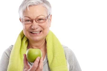 Healthy old woman holding green apple, smiling, towel around neck   65533; photo