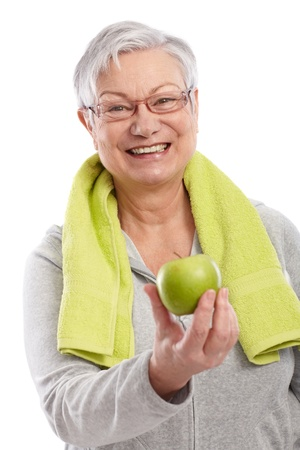 woman in towel: Old lady after workout holding green apple, smiling   65533;