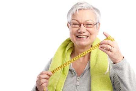 Fit old lady holding tape measure after workout, smiling   65533; photo